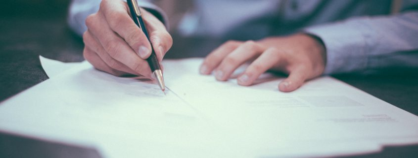 A photograph of a man writing on a piece of paper for our chartered status article
