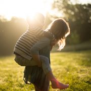 A photograph of a woman with a child on her back outdoors on a pension transfers article