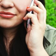 A photograph of a close up of a woman with a phone to her ear for our scam calls article